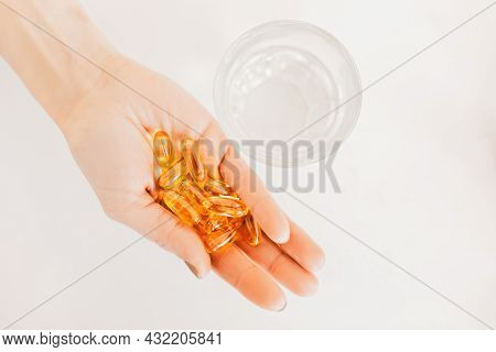 Girl Holding Capsules Pills Of Dietary Supplements With Omega And Amino Acids On A White Background.