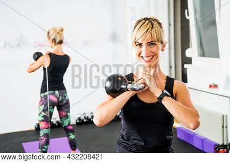 Adult Woman Is Practicing Kettlebell Pilates In Gym.