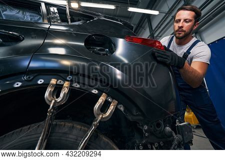 Screw Clamps Flattening Car Body While Technician Adjusting Taillight
