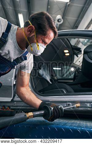 Tense Man Using Sliding Hammer For Straightening Car Surface