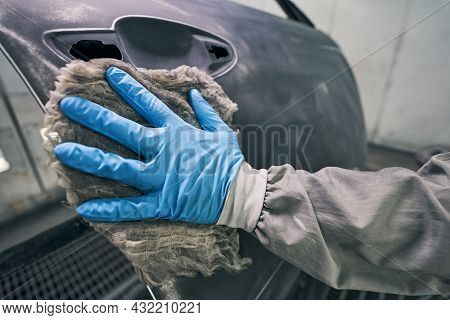 Person In Rubber Glove Wiping Car With Rag
