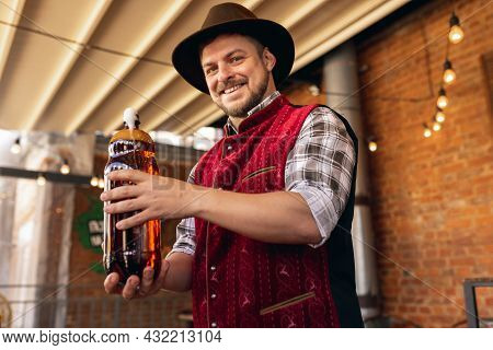 Caucasian Bearded Man, Owner Of Restaurant In Traditional Bavarian Festive Costume Presents Craft Be