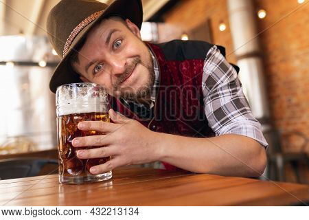Happy Smiling Man, Waiter In Traditional Austrian Or Bavarian Costume Holding Mug, Glass Of Dark Bee