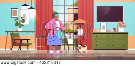 Elderly Woman Watering Flowers From Watering Can Senior African American Housewife Taking Care Of Ho