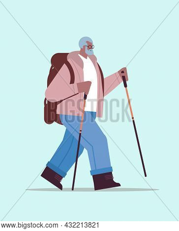 Senior African American Man Hiker Traveling With Backpack And Sticks For Walk Nordic Walking Active