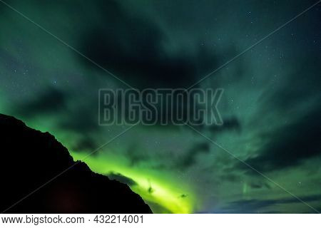Silhouette of a mountain against a clear sky with many stars and the Aurora Borealis, Northern Lights caused by the interaction of charged particles from the sun with atoms in the atmosphere. Iceland