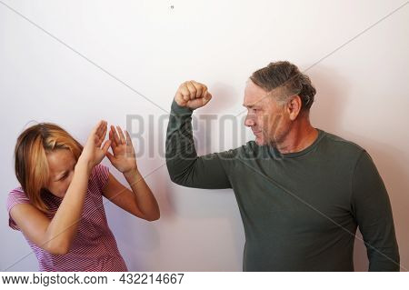Father Threatens His Teenage Daughter With His Fist. The Frightened Girl Covers Her Head With Her Ha