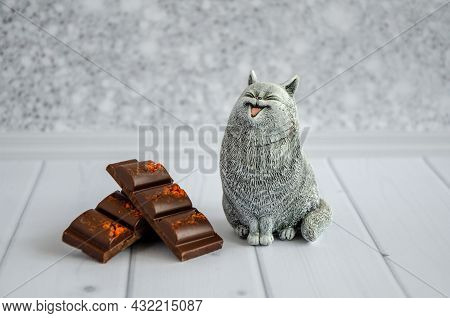 Cute Funny Toy Cat With A Smile Looks At A Delicious Sweet Chocolate Bar Lying Nearby. Concept: Diet