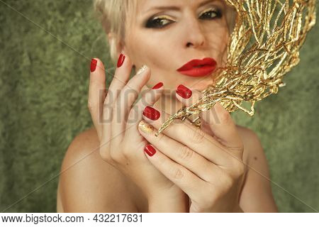 The Woman Is Blonde With Short Red Nails And Lips.