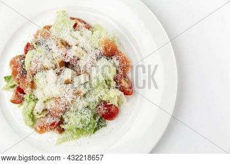 Caesar Salad With Salted Fish On A White Plate. Traditional Festive Snack. Close-up. White Backgroun