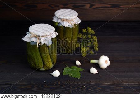 Pickled Cucumbers In A Jars On A Dark Wooden Background. Homemade Marinated Cucumbers.