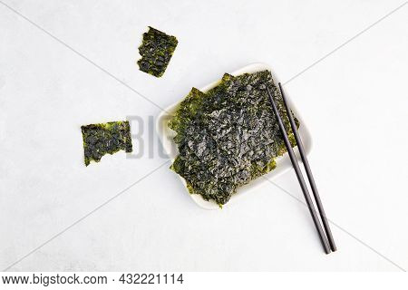 Crispy Nori Seaweed On Bowl With Chopsticks. Healthy Snack. Traditional Japanese Dry Seaweed Sheets.