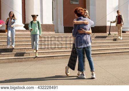 Happy and affectionate mom and daughter embracing by school building in the morning