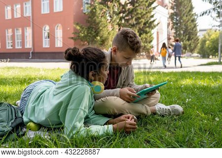 Two schoolkids in casualwear watching curious video in the net while having rest after school