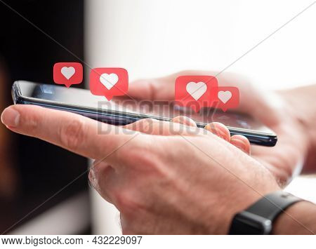 Person Getting Likes On Social Media, Close-up Of Hands Holding Smartphone With Heart Icons Hovering