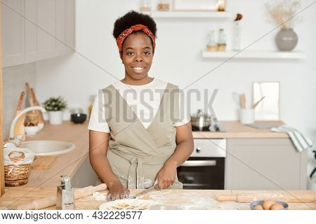Young African housewife cutting homemade dough for pastry by kitchen table