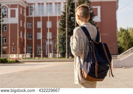 Youthul schoolboy with black backpack moving to school on sunny morning