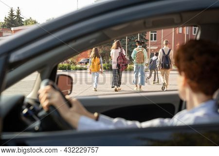 Group of schoolkids with backpacks moving along street while young female in car looking at them