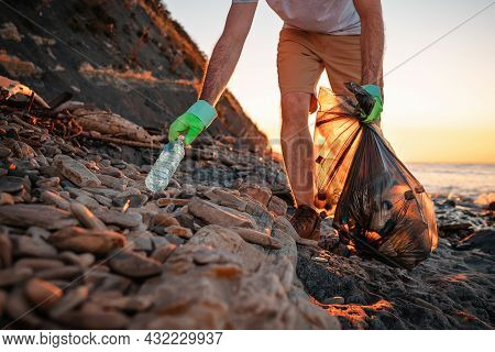 World Environment Day. A Male Activist Picks Up A Plastic Bottle On The Beach. In The Background, Th