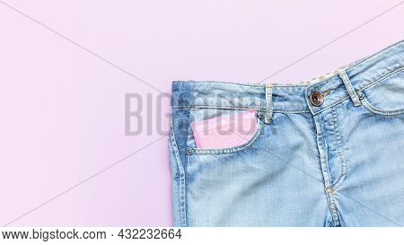 Menstruation Sanitary Pad In Pink Packaging In Pocket Of Light Blue Jeans On Pink Background.feminin