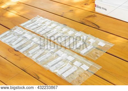 A Lot Of Coronavirus (covid-19) Test Result In The Zip Bags Are Arranged On Wood Table At Outdoor Fi
