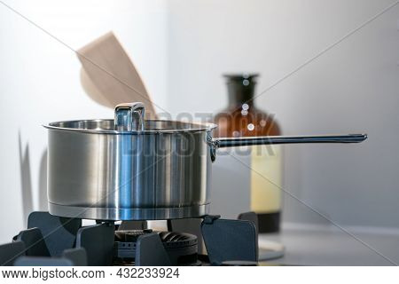 Stainless Steel Pot On Electronic Modern Flat Stove In Low Light On Counter Kitchen Room