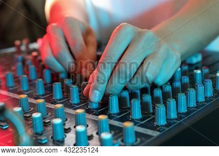 The Musician Adjusts The Sound On Audio Mixer