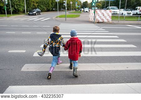 Children Cross The Road Through A Pedestrian Crossing. Zebra Crossing Strips