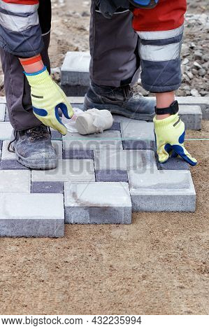 The Hands Of A Bricklayer In Protective Light Green Gloves Lay Out A Pattern Of Paving Slabs On A Sa
