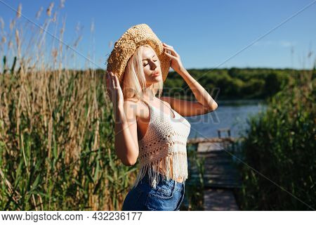 Beautiful Model Girl Posing On The Field Enjoying Nature Outdoors In A Straw Hat. Beauty Blond Young