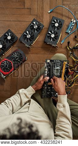 Close Up Top View Of African American Guy Sit On Floor Fix Computer Equipment Video Card. Ethnic Man