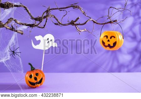 Halloween decorations with pumpkins, spider, spider web, ghost and bat on purple background. Halloween party concept.