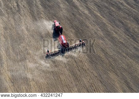 A farmer in a tractor prepares land with a sowing cultivator as part of pre-sowing work at the beginning of the spring agricultural season on agricultural land.