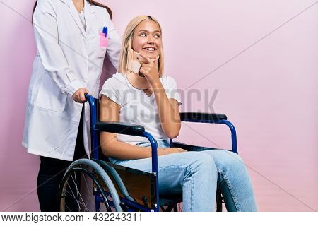 Beautiful blonde woman sitting on wheelchair with collar neck with hand on chin thinking about question, pensive expression. smiling with thoughtful face. doubt concept.