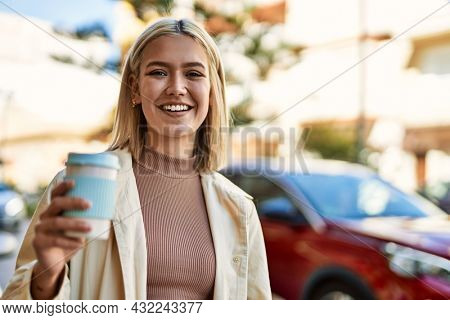 Young blonde girl smiling happy drinking take away coffee at the city.