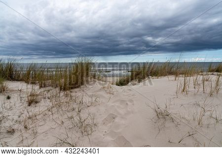 Landscape Of Grass And Sand Dunes With A Beach And Ocean Behind Under An Expressive Cloudy Sky