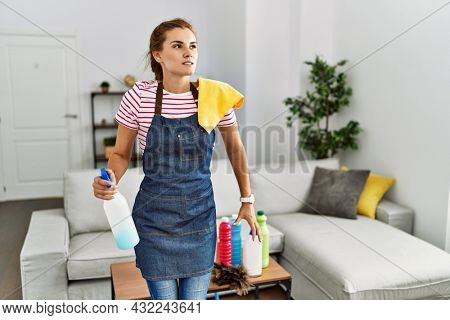 Young brunette woman wearing apron holding cleaning products at home angry and mad screaming frustrated and furious, shouting with anger. rage and aggressive concept.