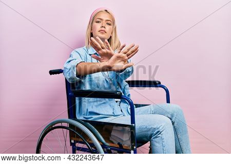 Beautiful blonde woman sitting on wheelchair rejection expression crossing arms and palms doing negative sign, angry face