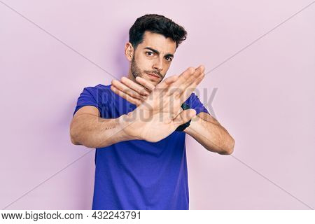 Young hispanic man wearing casual t shirt rejection expression crossing arms doing negative sign, angry face