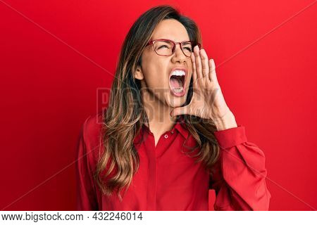 Young latin woman wearing casual clothes and glasses shouting and screaming loud to side with hand on mouth. communication concept.