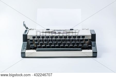 Old Vintage Typewriter And A Blank Sheet Of White Paper Inserted. Isolated On White Background.