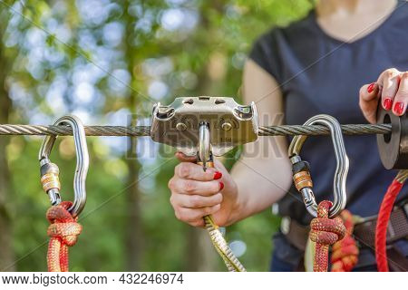 Woman Hangs A Carabiner On A Rope In A Forest Adventure Park. Using Climbing Equipment: Carabiner, B