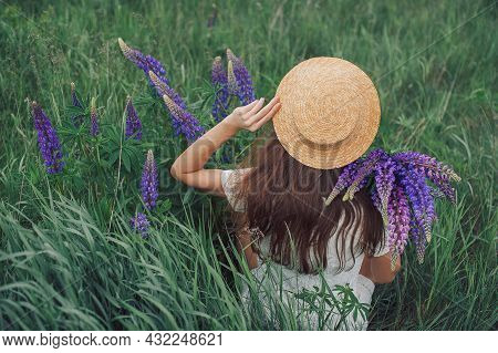 Beautiful Romantic Woman With Bouquet Of Lupines Joyfully In White Dress And Hat Sits In Field Of Pu