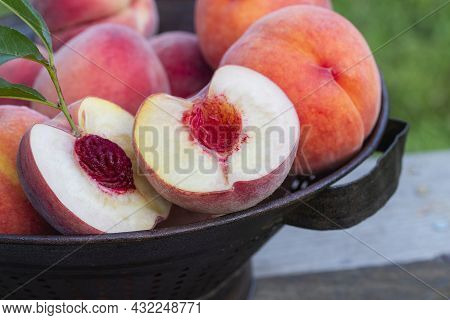 Fresh Cut And Split Peach With Stem And Leaves In A Colander With Whole Peaches.