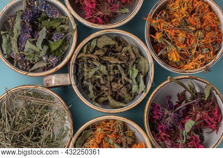 Assortment Of Dried Relaxing Tea Herbs In Colourful Cups On Blue Background Close Up. Calendula, Min