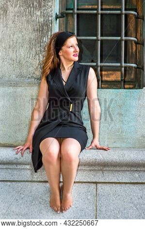 Sexy Woman Sitting Outside. Wearing A Black Sleeveless Trench Coat Dress, A Hair Band,  A Young Beau