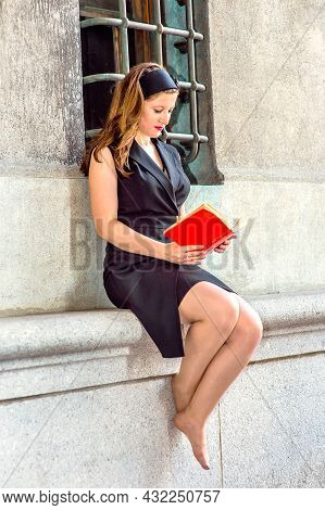 Sexy Woman Reading Outside. Wearing A Black Sleeveless Trench Coat Dress, A Hair Band,  A Young Beau