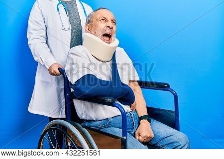 Handsome senior man with beard sitting on wheelchair with neck collar angry and mad screaming frustrated and furious, shouting with anger. rage and aggressive concept.