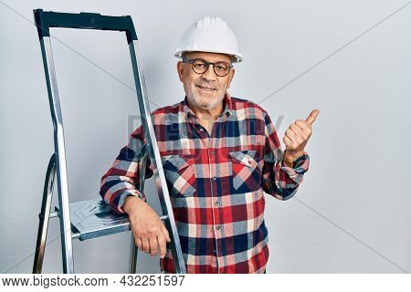 Handsome mature handyman close to construction stairs wearing hardhat pointing to the back behind with hand and thumbs up, smiling confident