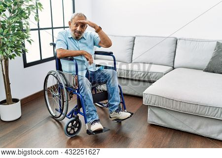 Handsome senior man sitting on wheelchair at the living room very happy and smiling looking far away with hand over head. searching concept.